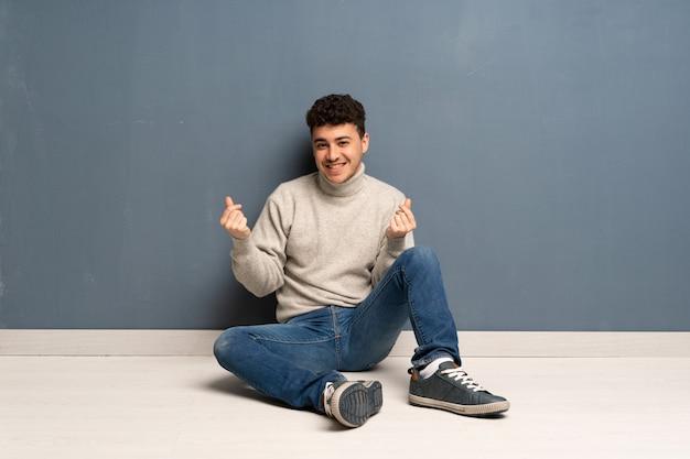 Jovem sentado no chão fazendo dinheiro gesto