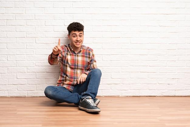 Jovem sentado no chão, mostrando e levantando um dedo em sinal dos melhores