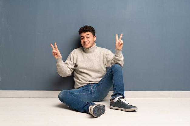 Jovem sentado no chão mostrando sinal de vitória com as duas mãos