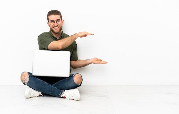 Jovem sentado no chão segurando copyspace para inserir um anúncio