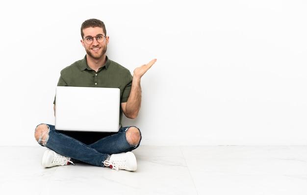 Jovem sentado no chão segurando o imaginário de copyspace na palma da mão para inserir um anúncio