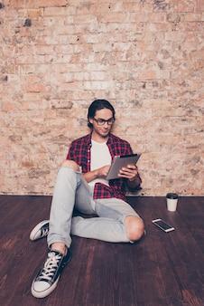 Jovem sentado no chão usando tablet digital