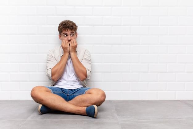 Jovem sentado no chão