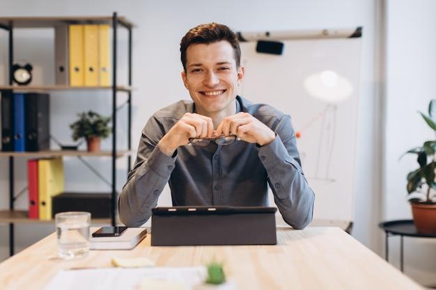 Jovem sentado no escritório e trabalhando no pc desktop. homem de negócios que olha o monitor do computador ao trabalhar no escritório.