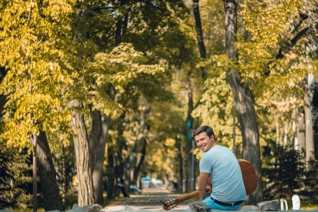 Jovem sentado no parque tocando violão. o homem younge gosta de música ao vivo em dias de sol