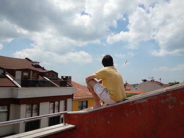Jovem sentado no telhado de uma casa, apreciando a vista das gaivotas da cidade velha voando no céu nublado de verão