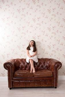 Jovem sentado num sofá de couro