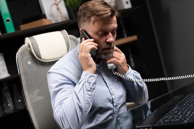 Jovem sentado segurando telefone fixo e telefone celular