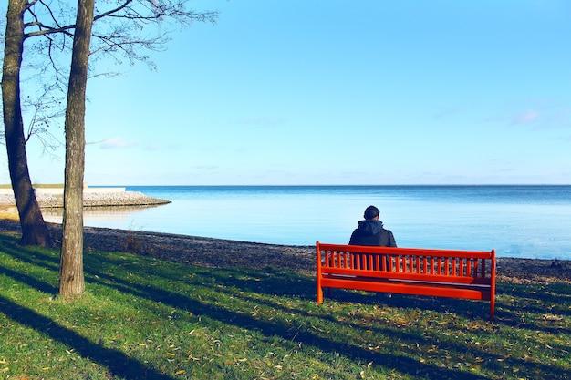 Jovem sentado sozinho em um banco em frente ao mar