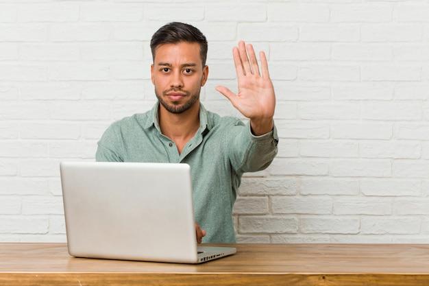 Jovem sentado trabalhando com seu laptop em pé com a mão estendida, mostrando o sinal de stop, impedindo-o