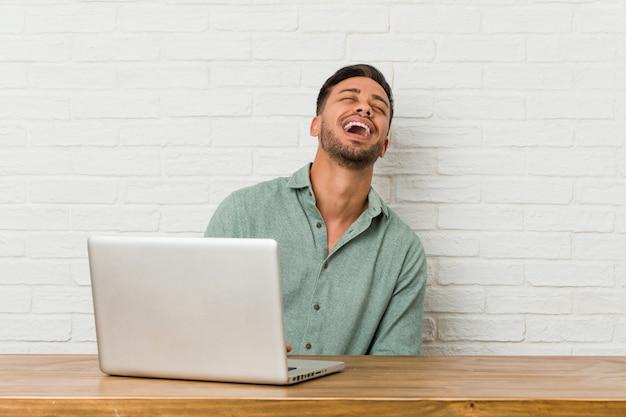 Jovem sentado trabalhando com seu laptop relaxado e feliz rindo, pescoço esticado, mostrando os dentes.