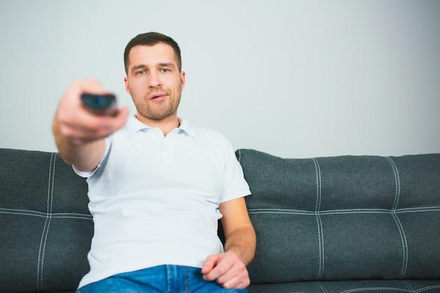 Jovem sente-se na sala usando o controle remoto, segurando-o com uma mão. cara sente-se sozinho e mudar de canal de tv.