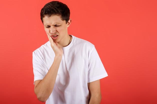Jovem sentindo dor, segurando sua bochecha com uma mão, sofrendo de dor de dente