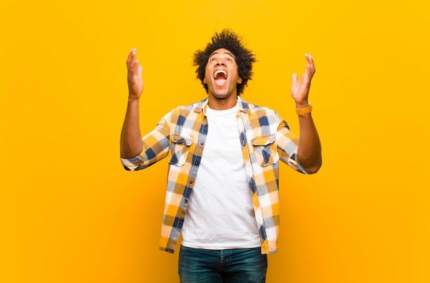 Jovem, sentindo-se feliz, espantado, sortudo e surpreso, comemorando a vitória com as duas mãos no ar por cima do muro laranja