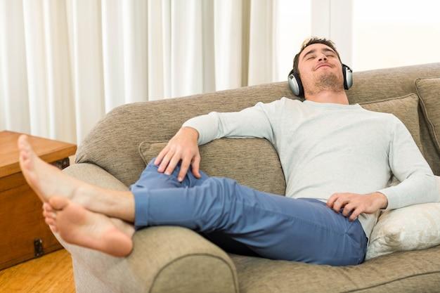 Jovem, sentindo-se relaxado enquanto ouve música com fones de ouvido na sala de estar