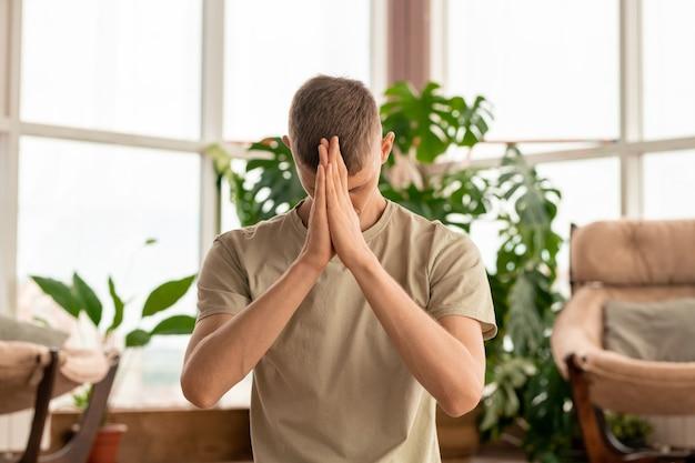 Jovem sereno e concentrado em roupas esportivas, mantendo as mãos juntas na testa enquanto pratica meditação em casa