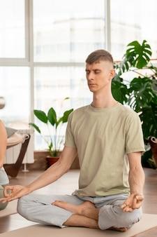 Jovem sereno em roupas esportivas cruzando as pernas enquanto está sentado na esteira em pose de lótus e praticando exercícios de meditação em casa