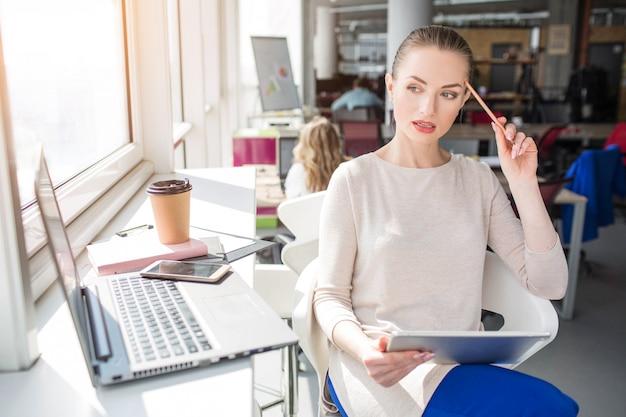 Jovem séria e atenciosa está pensando. ela está olhando para a direita. ela também tem um tablet nas mãos e um laptop na mesa.