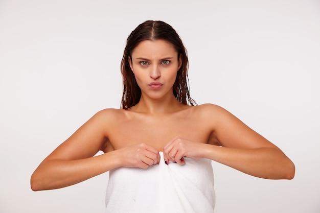Jovem séria e atraente mulher de cabelos escuros enrolada em uma toalha branca em pé sobre um fundo branco, sobrancelhas franzidas e lábios enrugados enquanto olha para a câmera