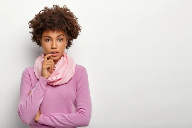 Jovem séria e encaracolada com cabelo afro escuro, mantém os braços parcialmente cruzados e usa um decote de polonê roxo