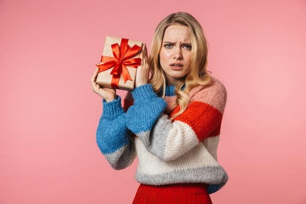 Jovem, séria, muito bonita, mulher posando isolada sobre uma parede rosa segurando uma caixa de presente