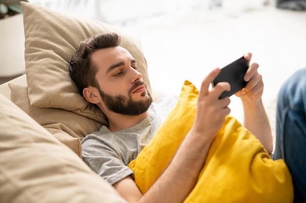 Jovem sério barbudo com almofada amarela deitado no sofá e assistindo a um vídeo da internet no smartphone em quarentena