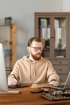 Jovem sério barbudo de óculos desenhando o esboço do projeto em uma mesa digitalizadora e editando-o no laptop