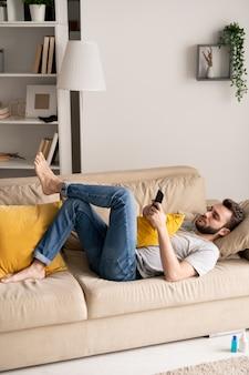 Jovem sério barbudo deitado em um sofá confortável e usando o smartphone em isolamento doméstico