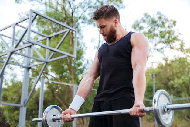 Jovem sério barbudo fitness levantando barra ao ar livre