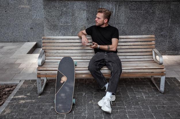 Jovem sério com longboard sentado no banco em localização de cidade moderna, olhando para a distância segurando o smartphone, navegar na internet, ler notícias, curtir postagens. conceito de lazer ao ar livre.