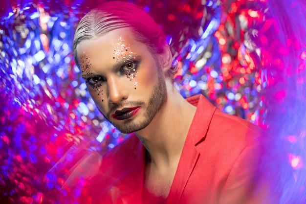 Jovem sério com maquiagem de palco, cabelo branco com penteado preciso e uma elegante jaqueta vermelha sobre o corpo nu, olhando para você no fundo colorido