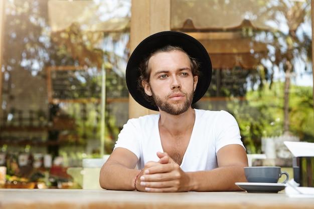 Jovem sério de chapéu, olhando para a distância com uma expressão de rosto chateado e infeliz enquanto está sentado sozinho na mesa do café com uma xícara de chá, esperando pela namorada