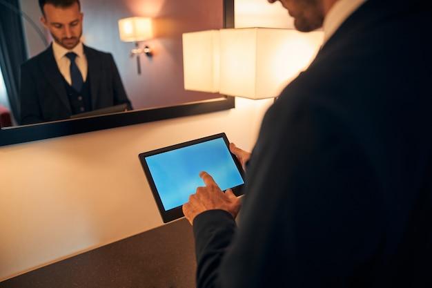 Jovem sério de terno em frente a um espelho e olhando para a tela de um tablet ao tocá-lo. banner do site