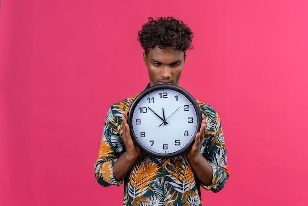 Jovem sério e severo de pele escura com cabelo encaracolado e camisa estampada de folhas segurando um relógio de parede mostrando as horas em um fundo rosa