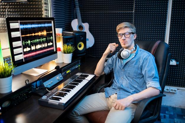 Jovem sério em roupas casuais sentado na poltrona perto da mesa com o monitor do computador e o teclado enquanto mixa sons no estúdio