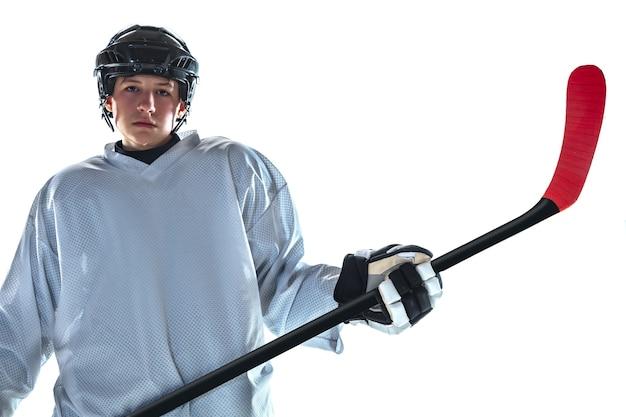 Jovem sério jogador de hóquei com o taco na quadra de gelo e parede branca