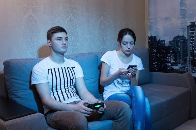 Jovem sério jogando videogame com a namorada que o ignora e navega na internet pelo celular, sentado no sofá em frente a uma tv em casa