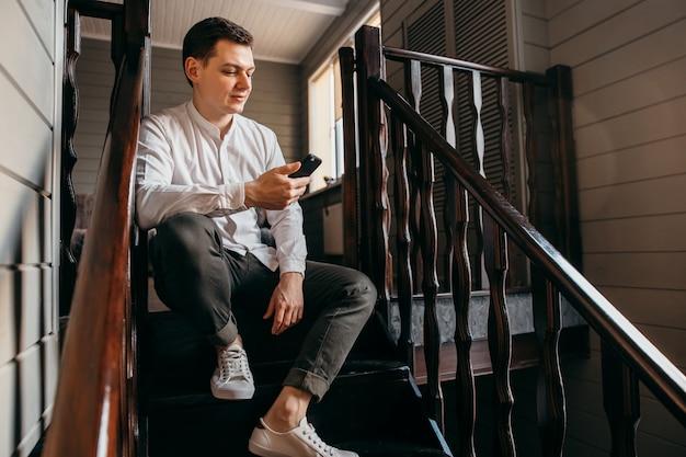 Jovem sério sentado na escada e olhe para o telefone móvel.
