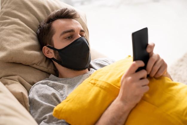 Jovem sério usando máscara protetora deitado com travesseiro no sofá e usando o smartphone enquanto lê notícias sobre coronavírus