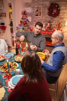 Jovem servindo vinho para o pai no jantar de natal em família. celebração de natal com comida deliciosa.