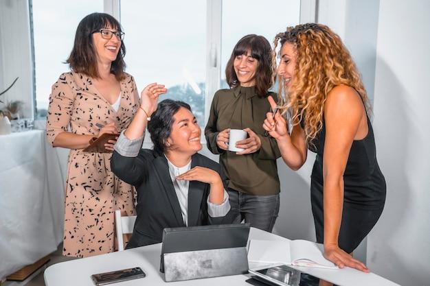 Jovem sessão empreendedora no escritório, chefe de um grupo étnico latino, dando ordens a três jovens mulheres caucasianas ao lado dela