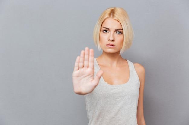 Jovem severa e séria mostrando um gesto de pare sobre uma parede cinza