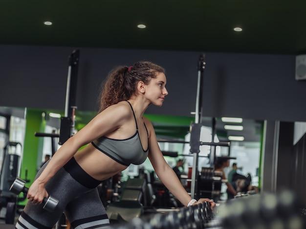 Jovem sexy apta a mulher com roupa esportiva, fazendo exercícios de extensão com halteres com uma mão apoiada na prateleira no ginásio. treinamento de peso livre