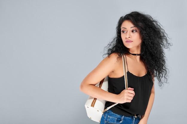 Jovem sexy com cabelo preto encaracolado carregando uma mochila branca com zíper dourado. ela usa um top preto claro e jeans azul.
