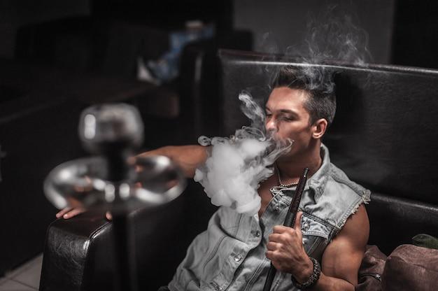 Jovem sexy fumando narguilé e fumaça saindo da boca em restaurante árabe.