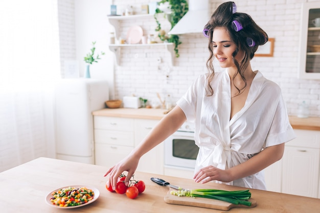 Jovem simpática atraente cozinhando na cozinha. fique na mesa e pegue pimenta vermelha cortada. cebola verde é cortada na mesa. mistura de legumes no prato. trabalhando em casa. vida descuidada.