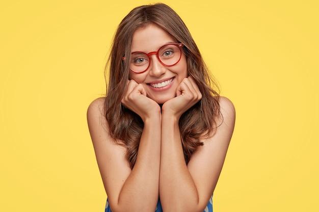 Jovem simpática com óculos posando contra a parede amarela