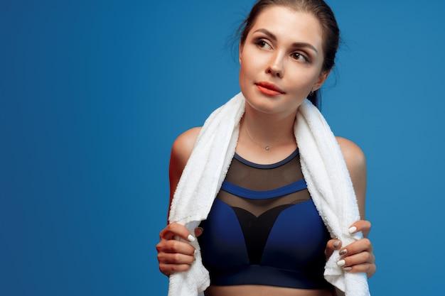 Jovem simpática com roupas de esporte, segurando uma toalha no ginásio