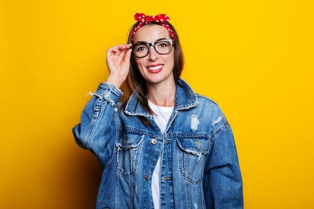 Jovem simpática com uma faixa de cabelo, uma jaqueta jeans, segurando os óculos em uma superfície amarela
