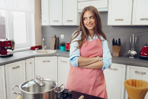 Jovem simpática cozinhando algo perto do fogão na cozinha